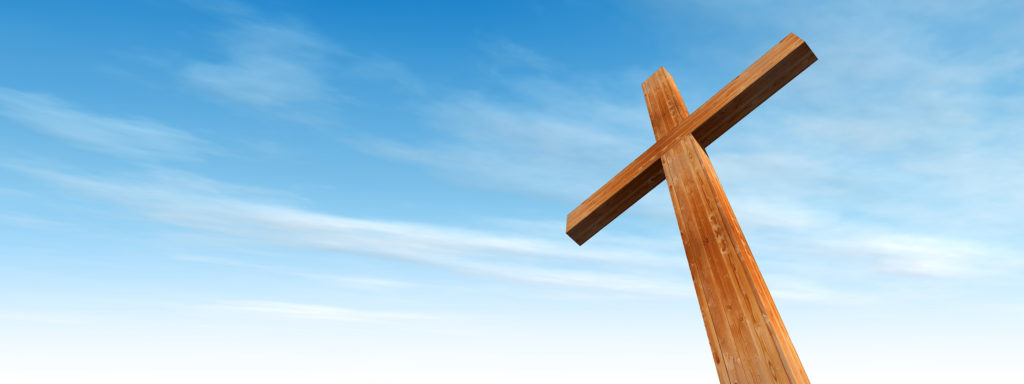 Concept or conceptual wood cross or religion symbol shape over a blue sky with clouds background banner